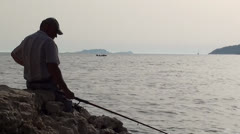 Man sitting and fishing zoom out Stock Footage