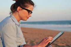 Businesswoman working on tablet computer on the beach NTSC Stock Footage