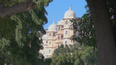 India Rajasthan Udaipur City Palace domes through gap in trees 47 Stock Footage