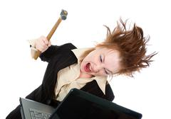 stressed businesswoman smashing her laptop with a hammer - stock photo
