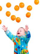 little baby girl caughts flying oranges - stock photo