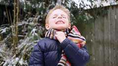 Boy playing in snow in garden Stock Footage