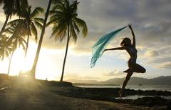 silhouette of young woman jumping at las galeras beach - stock photo