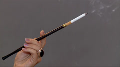 Woman's hand with cigarette in mouthpiece Stock Footage