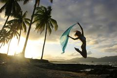 Silhouette of young woman jumping at las galeras beach Stock Photos