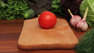 Woman's hands cut tomato on a wooden board Stock Footage