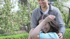 Young female on swing in park with boyfriend Stock Footage