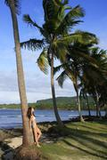young woman in bikini standing by palm tree, las galeras beach - stock photo