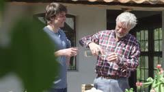 Men having drink in garden Stock Footage