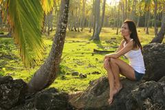 young woman sitting on rocks in coconut trees grove, las galeras beach - stock photo
