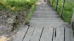 Woman in red shorts climb wooden stairs in park Stock Footage