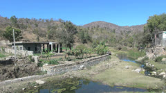 India Rajasthan Ranakpur house near retaining wall on creek Stock Footage