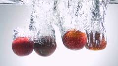 Fresh plum dropped into water Stock Footage