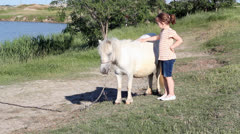 Little girl and pony horse pet Stock Footage