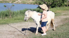 Little girl and white pony horse Stock Footage