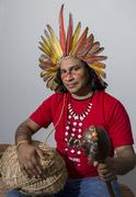roni wasiry guará with traditional headdress, hand basket and musical instru - stock photo