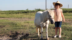 Little girl with cowboy hat and pony horse Stock Footage