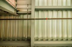 exposed underside of steel floor or roof deck with utilities and spray-on fir - stock photo