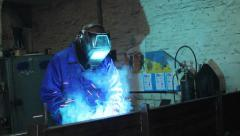 Stock Video Footage of Male wearing uniform welds with welding machine torch