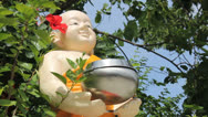 Stock Video Footage of Man Gives Donation To Chubby Buddhist Statue