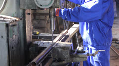 Drilling holes in steel bar girder at factory construction site - stock footage