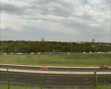 Commuting traffic speeding at highway + traffic jam in background Stock Footage