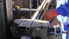 Male in gloves drills holes in steel girder bar at factory - stock footage