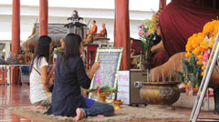 Two Women Pay Respects At Buddhist Temple Stock Footage