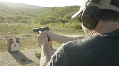 Shooting a pistol with hearing protection Stock Footage