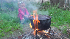 Child Waiting Food Cooking in a Pot for Eating, Rustic Cooking in Yard, Children Stock Footage