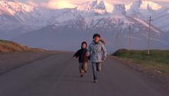 Children run into the setting Sun - stock footage