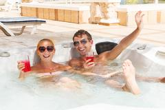 Young couple relaxing in jacuzzi pool - stock photo