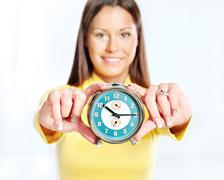 woman showing alarm clock - stock photo