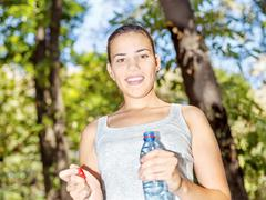girl in forest holding bottle of water - stock photo