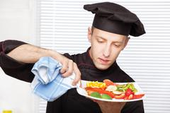 chef cleaning edge of plate with cloth - stock photo
