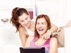 Stock Photo of happy teenage girls using touchpad