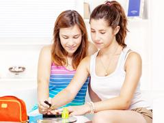 Teenage girls polishing fingernails Stock Photos