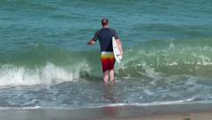 Surfer enters the water Stock Footage