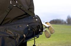 Golfclubs in black bag on back of golfer Stock Photos