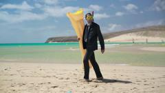 Businessman walking on the beach with inflatable mattress and snorkeling mask - stock footage