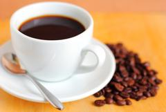 White cup of coffee with coffee beans Stock Photos