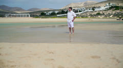 Man in white clothes walking on the beach Stock Footage