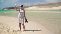 Young businesswoman with cellphone standing on the beach Stock Footage