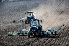 Tractors with sowers on the field Stock Photos
