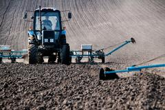 Tractor with sower on the field Stock Photos