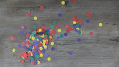 A hand scatters colorfull confetti on a wooden ground g130008 Stock Footage