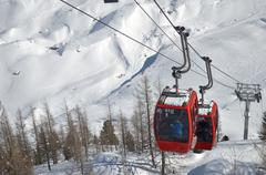 Cablecars moving up snow covered mountain Stock Photos