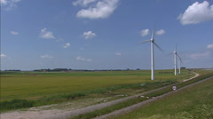 Pan + hold Wind turbines in rural landscape + sea dike Stock Footage