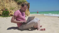 Stock Video Footage of Young man working on laptop on beautiful beach HD