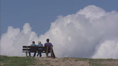 People sit on bench at sea dike - close up Stock Footage